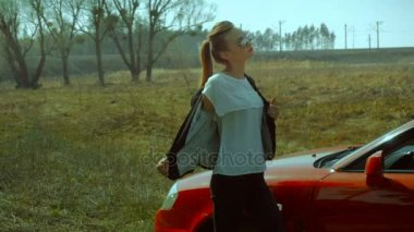 Girl takes off the jacket near red car in the field