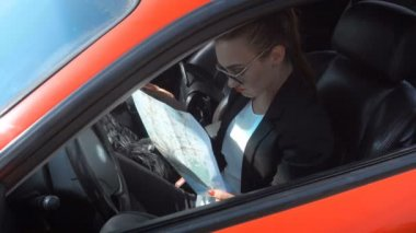 Girl driver sits in the car and studying a map of the area