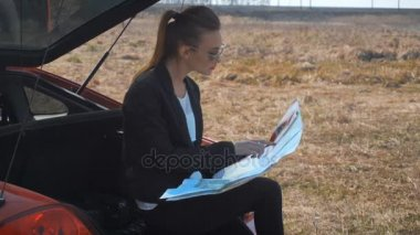 Girl sits in the trunk of a car and exploring the map