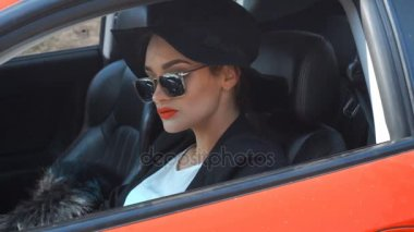 Stylish young girl driver driving a car