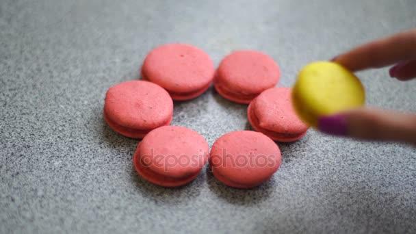 dívka dává žluté makronky na růžové