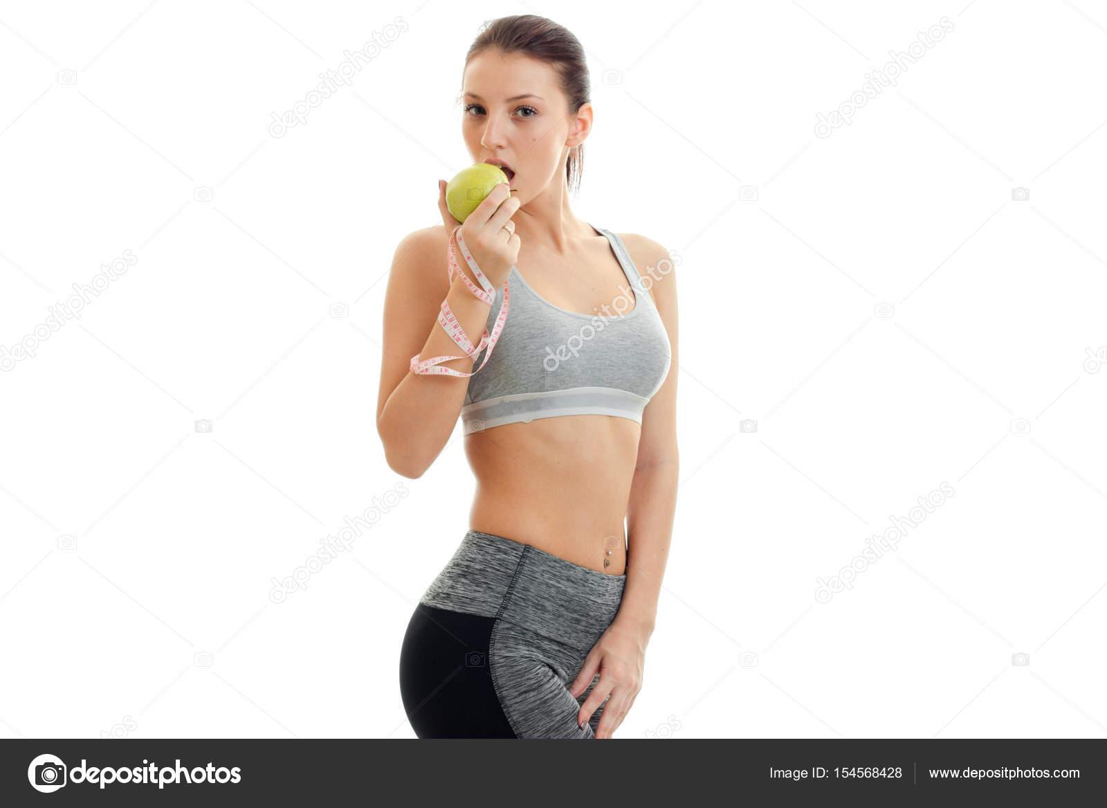 Fitness joven linda chica gris está parado lateralmente y come manzana verde  aislado sobre fondo blanco — Foto de ponomarencko c1cb0550adcd