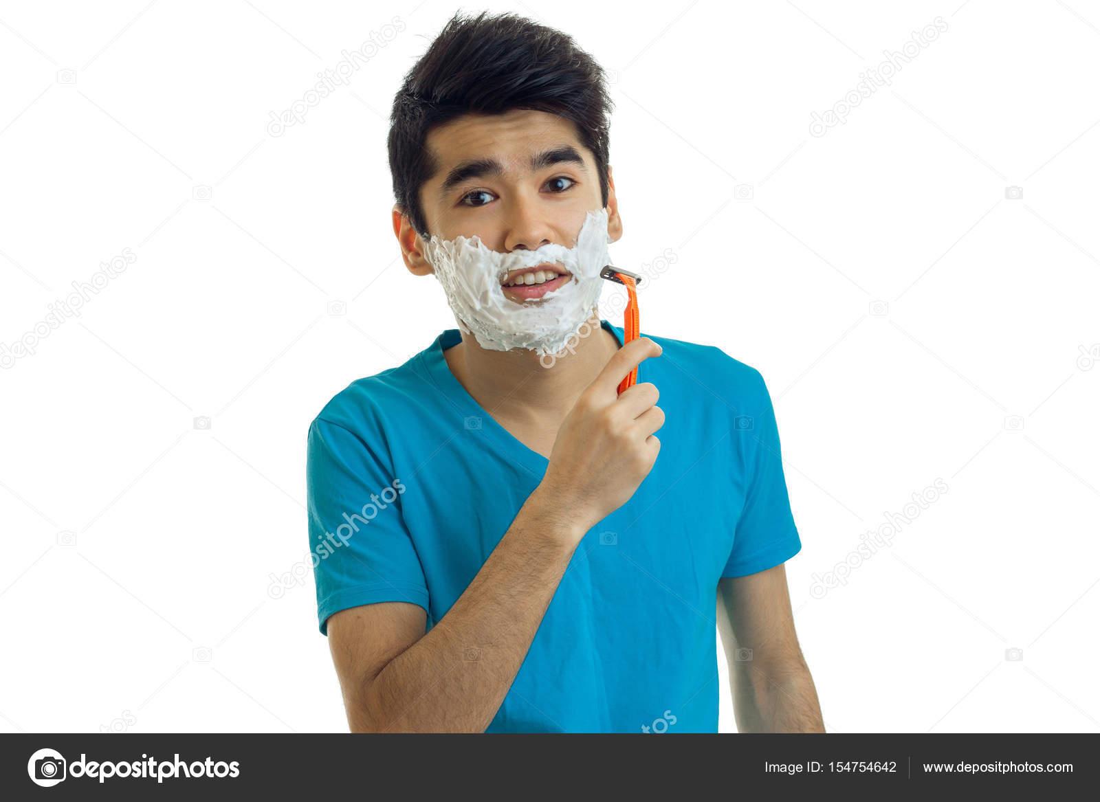 Söt ung kille i en blå t-shirt och med svart hår ser raka och rakar sitt skägg  maskin med skum i ansiktet isolerad på vit bakgrund — Foto av ponomarencko 1a26aa3c2ae7d