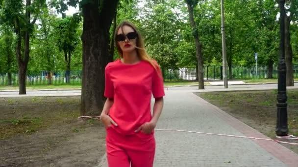Glamour mladá blond dáma v červeném obleku a sluneční brýle chodí po ulici