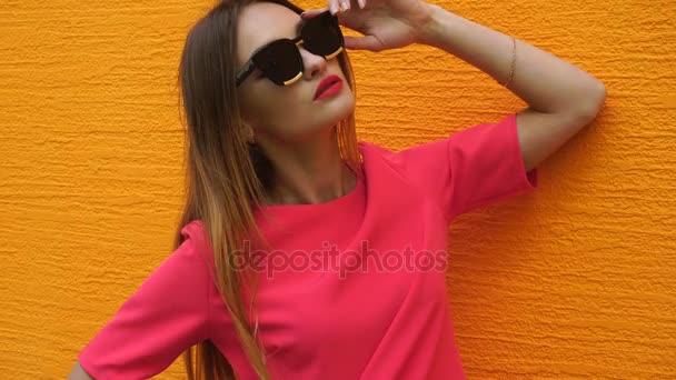 rozkošná mladá blond dáma v červeném obleku a černými brýlemi, které představují