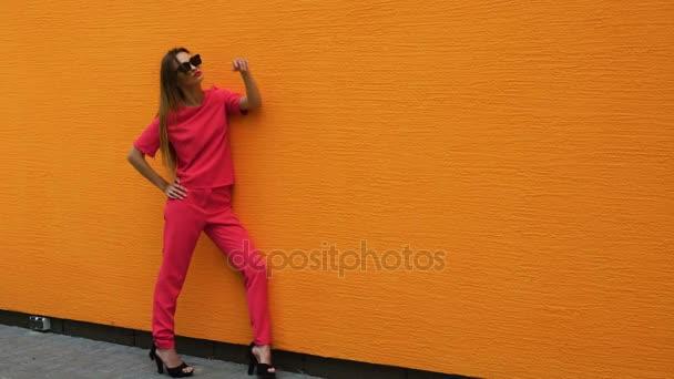 Modelka na vysokých podpatcích v červeném obleku a sluneční brýle, které vystupují po celé délce