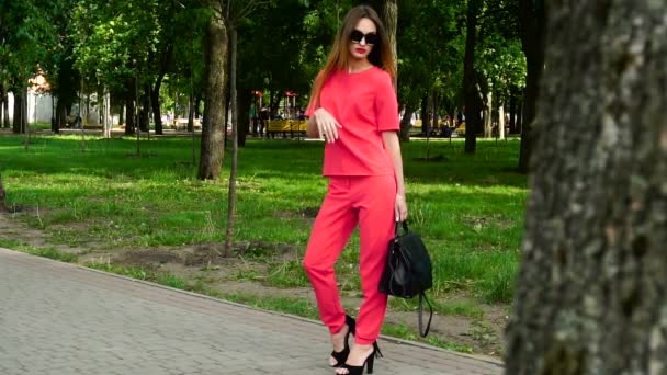 Sexy business woman on high heels in red suit and sunglasses