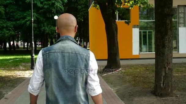Módní mladý muž v Džínové Oblečení chodí po ulici
