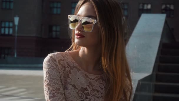 young sexual girl in glasses with long hair sitting on the street and turns her head back