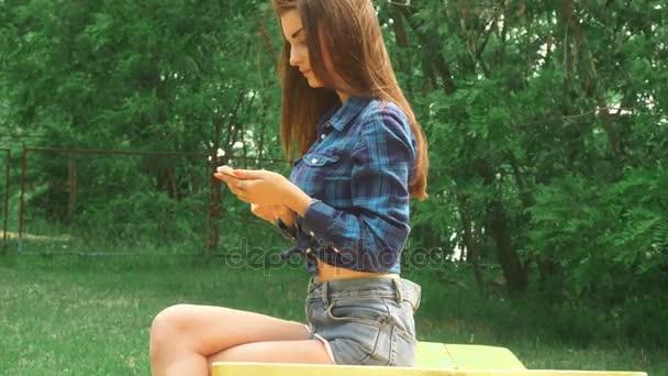 mladá dívka sedí na lavičce v parku a pomocí mobilního telefonu
