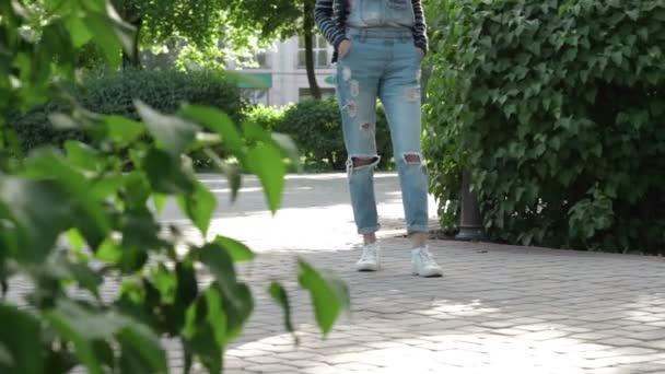 dívka v džínové overaly stojí v uličce