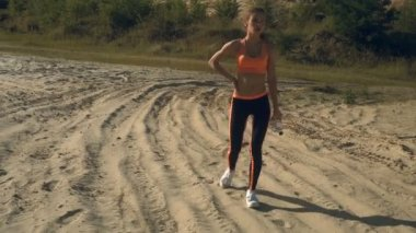 Sports lady after workout walks with water in bottle in her hands
