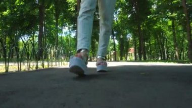 Girl on high heels with stripes walks at the park