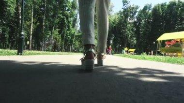 Elegant woman on high heels walks at the park