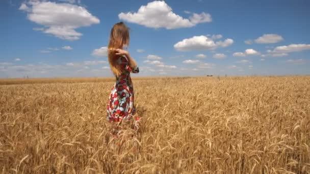Frau im Kleid steht mit Weizen in der Mitte des Feldes und glättet die Haare