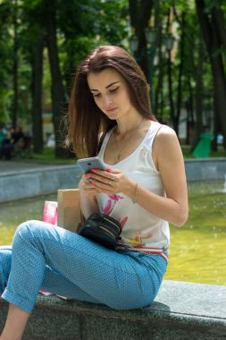 beautiful girl sitting near the fountain and stares at the phone