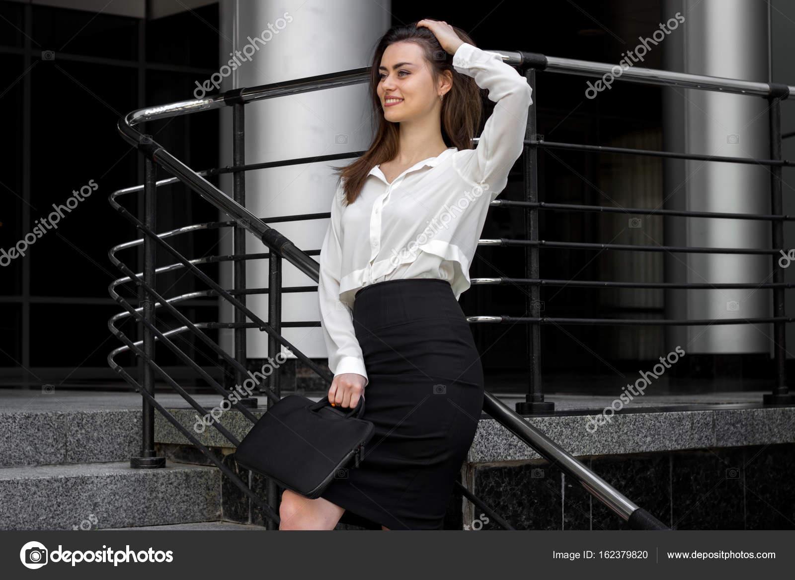4338ac6f95d1 Attraktive Business-Frau in weißem Hemd und schwarzer Rock steht auf ...