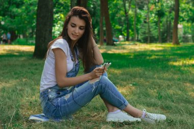 Smiling woman sitting on the grass and listen to the headphones music