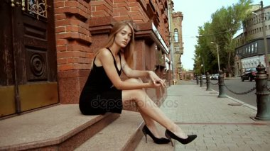 Charming pretty girl in black shoes and dress sits outdoors