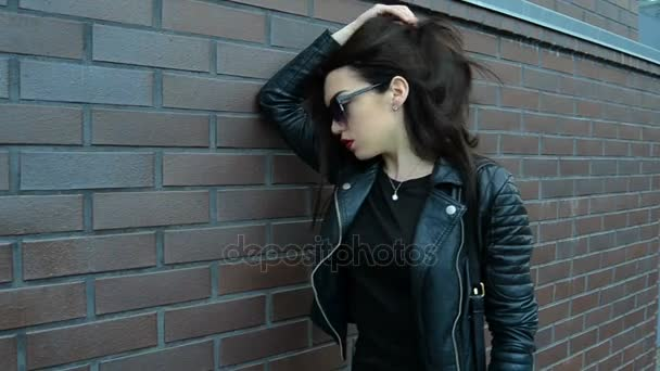 brunetka s červenou rtěnku v tmavých brýlích a koženou bundu, Pózování na kameru v blízkosti zdi