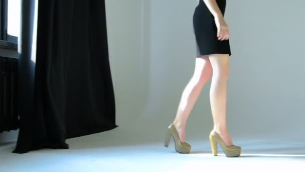 young girl with slender feet in shoes and black dress slowly walks on Studio