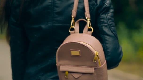 Frau in Lederjacke mit Rucksack auf der Schulter geht ins Freie