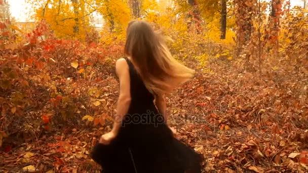 junges Mädchen in schwarzem Kleid dreht sich im herbstlichen Wald