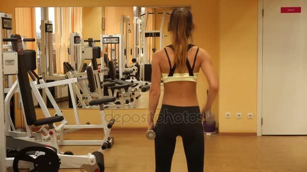 schlanke blonde Sportlerin, die in einem Fitnessstudio mit Hanteln übt