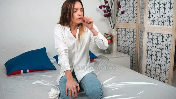 krankes Mädchen sitzt auf dem Bett und Husten zu Hause