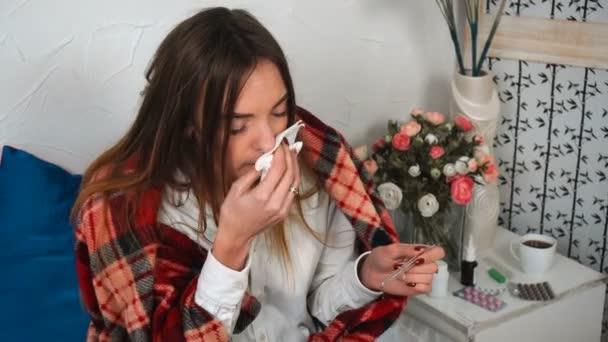 krankes Mädchen mit Schnupfen und Thermometer in der Hand zu Hause