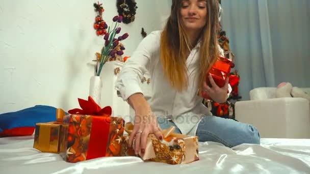 Veselá dívka poslouchá hudbu se sluchátky s bandou vánoční dárky