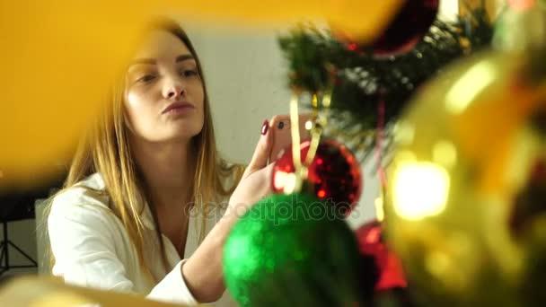 Krásná dívka zdobí vánoční strom