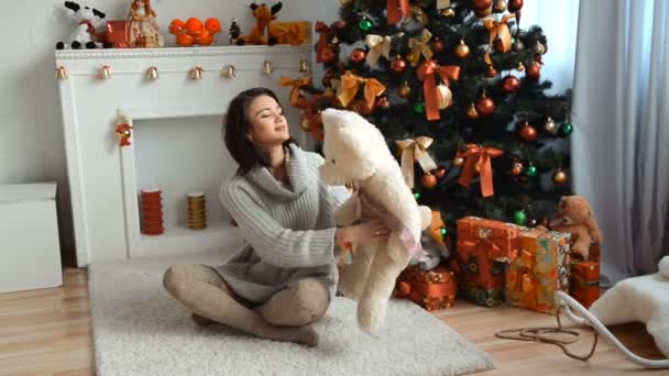 beautiful brunette in sweater sitting near a Christmas tree and holds a teddy bear