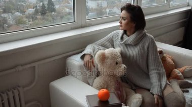 beautiful brunette sits on the couch with a teddy bear and looks out the window at home