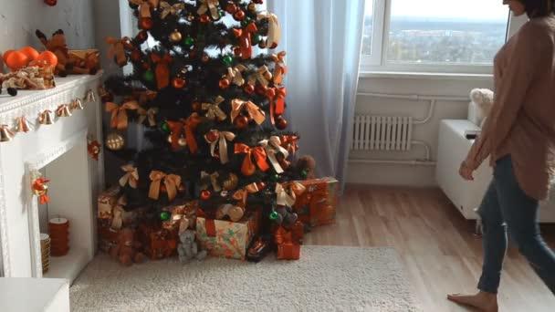 roztomilá mladá dívka na vánoční stromek má dar a odchází z domova