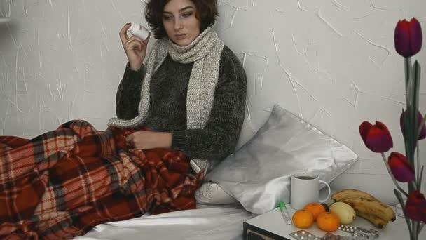 Nemocná žena leží v posteli s prášky pod přikrývkou doma