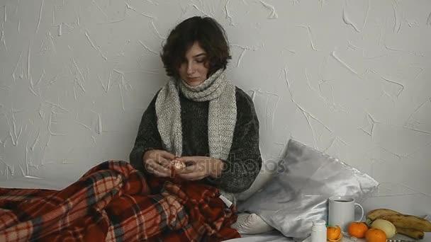 Kranke Frau im Pullover isst Mandarine zu Hause im Bett