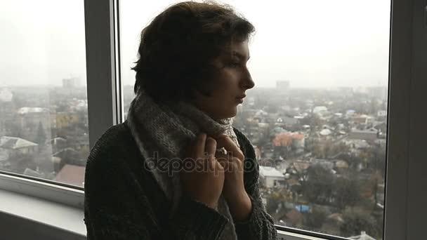 eine kranke Frau in Pullover schaut aus dem Fenster und Husten zu Hause