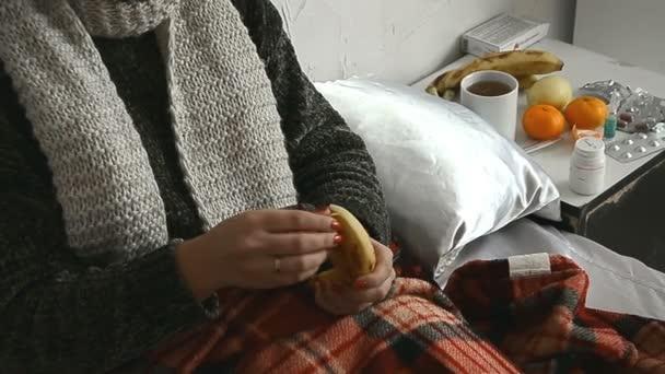 Nemocná dívka ve svetru leží v posteli a doma jí banány