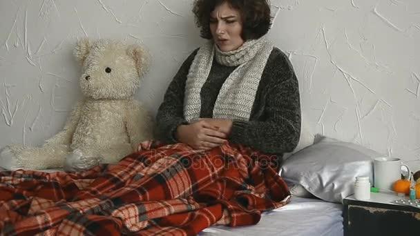 Kranke Frau liegt mit Bauchschmerzen zu Hause im Bett