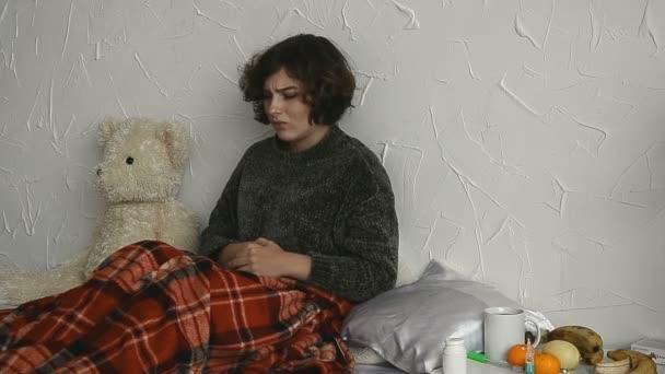 nemocná žena leží v posteli s bolesti břicha jí prášky doma