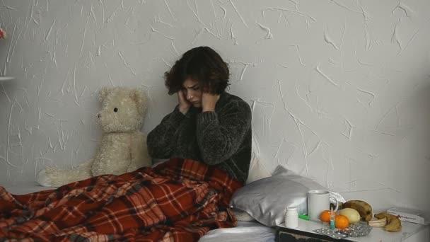 kranke Frau im Bett mit Kopfschmerzen zu Hause