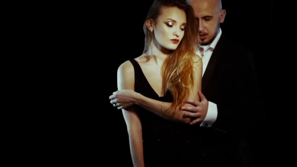 sexy young couple in suit and dress on black background