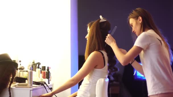 young hair stylist make hairstyle with beautiful woman