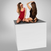 two hot girls sits on a cube in studio