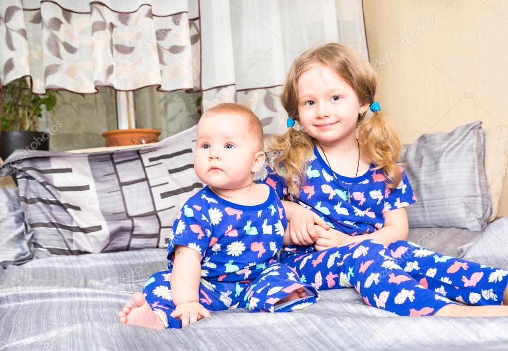 b198b7f6f3a4d Zwei Schwestern. Ältere Schwester Kind umarmt sein neugeborenes  Schwesterchen. Süße Kinder Mädchen im Bett