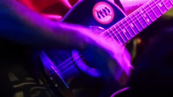 kytarista hraje na akustickou kytaru