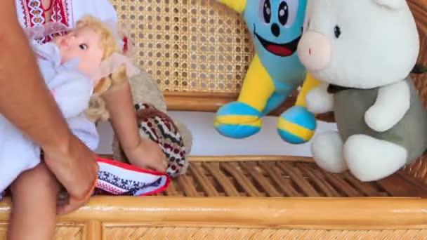 Closeup holčička v vyshyvanka hraje s hračkami a panenky na krajkové dřevěné křeslo
