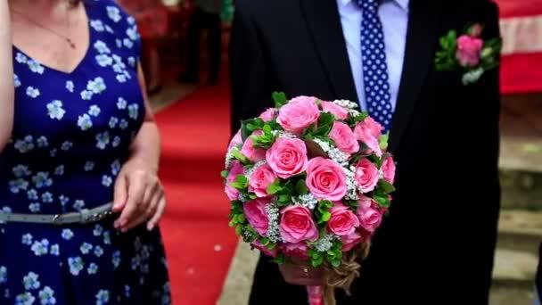 Ženich má svatební kytice z růžových růží