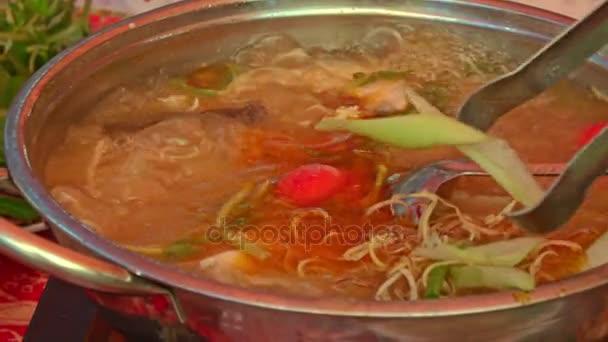 Člověk staví ingredience do varu rybí polévku ve velkém pánev na dušení